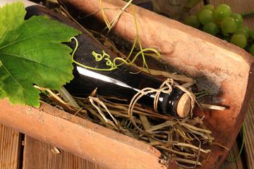 Weinflasche im Tonziegel auf Stroh