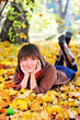 Woman lying on her stomach on autumn leaves.