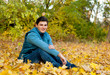 Young smiling man relaxing in autumn park.