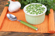 Plastic round bowl of cream with a tuft of parsley and garlic