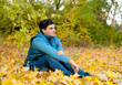 Guy relaxing in park, autumn outdoor.