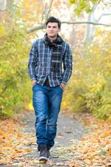 Smiling man walking in autumn park.