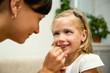 Женщина раскрашивает лицо ребенка к празднику