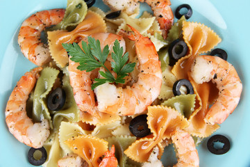 Fresh prawns with coloured macaroni and olives in a blue plate