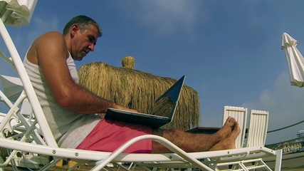 Smilling Man with Laptop Laying on Sunbed