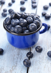 Delicious blueberries in cup on table close-up