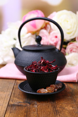 Black teapot, bowl and hibiscus tea