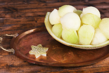 Melon in melon peel on metal tray on wooden background