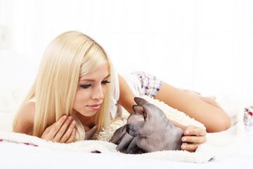 Beautiful young woman with gray sphinx cat lying on bed