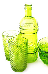 Green glass bottle, bowls and glasses, isolated on white