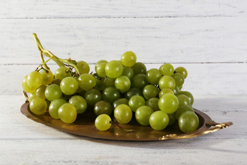 Green grape on tray on wooden background
