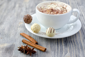 Pralines and a cup of cappuccino copy space wooden background