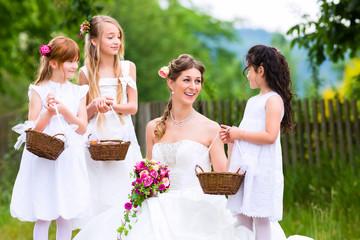 Braut im Brautkleid mit Blumenkindern