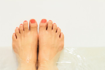Bath time. Woman feet in the water tub.