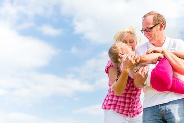 Familie tobt auf Feld oder Wiese