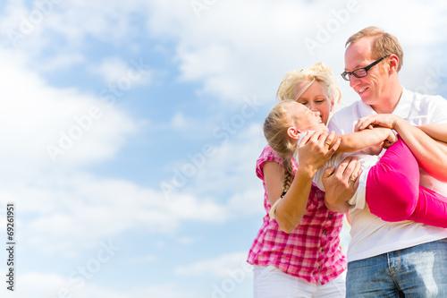 canvas print picture Familie tobt auf Feld oder Wiese