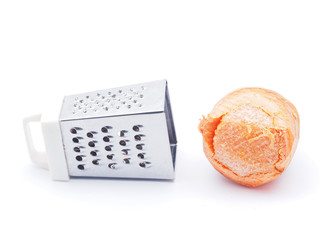 grater and carrots on a white background