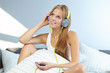 Blonde woman lying on bed while listening music through headphon