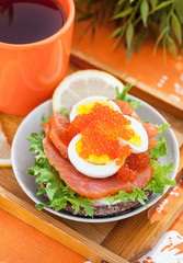 Sandwich with salted salmon, egg and red caviar