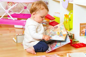 Kleinkind mit Bilderbuch im Kinderzimmer