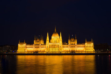 Budapest parliament building at night illuminated over the river