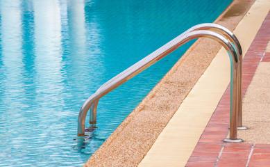 Steel ladder in a blue swimming pool