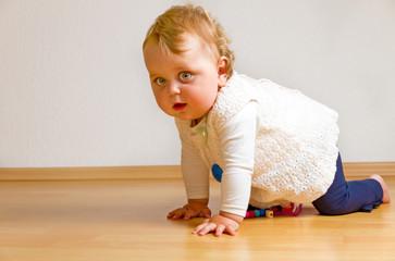 Baby auf dem Parkettboden