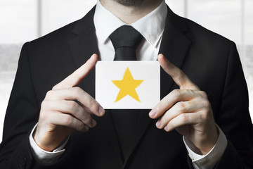 businessman holding sign rating star gold