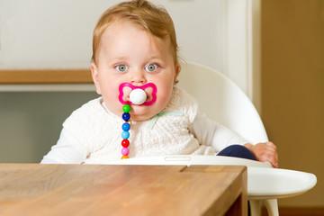 Baby mit Schnuller im Hochstuhl