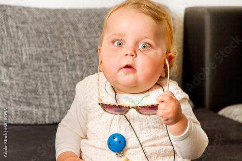 canvas print picture Baby mit Sonnenbrille in der Hand