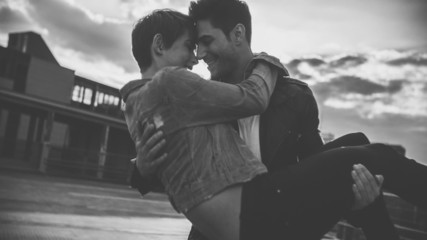 guy holding girl in his arms as they have a romantic moment