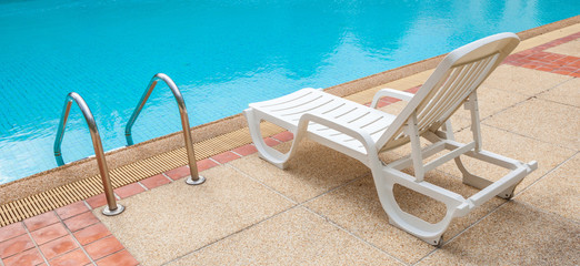 White lounge chair at the pool side near ladder; blue swimming p