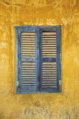 old faded blue and yellow rustic window
