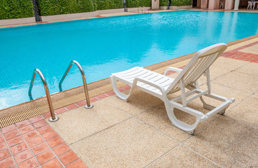 White lounge chair at the pool side near ladder, blue swimming p