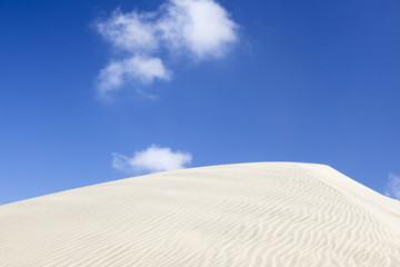Sand dune, white clouds and blue sky.