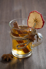 spiced apple cider in glass mug on a wooden table, vertical