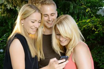Freunde schauen Fotos auf Smartphone