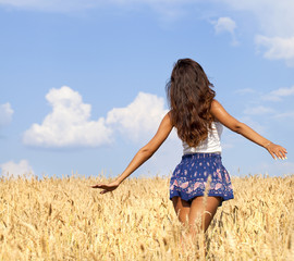 Young woman in a wheat golden field
