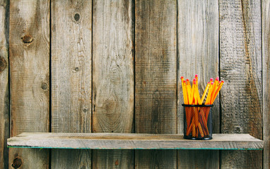 Pencils on a wooden shelf.