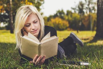 girl reading in park on grass