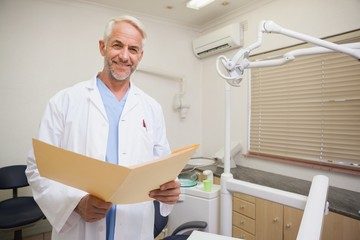 Dentist smiling at camera holding folder