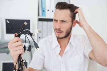 Confused computer engineer looking at wires
