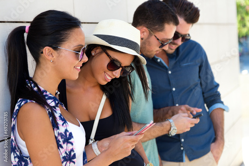 canvas print picture Portrait of group of friends having fun with smartphones.