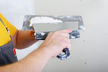 repairman works with plasterboard, prepairing plaster for plaste
