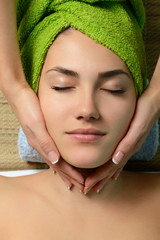 Young beautiful woman in spa gets a facial massage