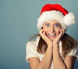 Portrait of surprised attractive cheerful girl in Santa's hat ha