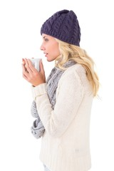 Pretty blonde in winter fashion holding mug