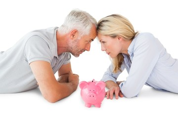 Happy couple lying with piggy bank