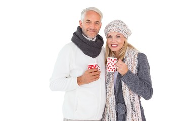 Happy couple in winter fashion holding mugs