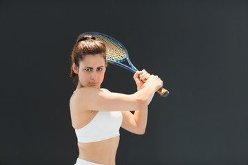 Portrait of confident female tennis player with racquet